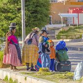 COPACABANA, BOLIVIA, MAY 6, 2014: Local women in traditional costumes and children wait with their luggage for the bus