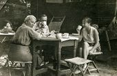 POLAND, CIRCA FORTIES: Vintage photo of parents with teenager daughter drinking tea in garden