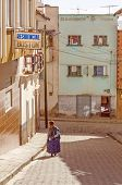 COPACABANA, BOLIVIA, MAY 6, 2014: Local woman in traditional costume and bowler hat walks down the street