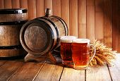 Beer barrel with beer glasses on table on wooden background