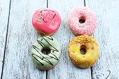 Delicious donuts with glaze on colorful wooden background