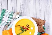 Pumpkin soup in white plate and pumpkin slice on napkin, on wooden background