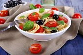 Spaghetti with tomatoes, olives and basil leaves on plate on napkin on wooden background