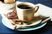 Cup of coffee with tasty cookies on color wooden background
