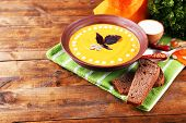 Pumpkin soup in color plate and pumpkin slice on napkin, on wooden background