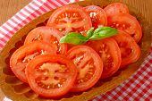 detail of tomato slices and fresh basil on oval wooden plate and checkered dishtowel