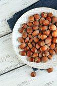 Hazelnuts on plate on napkin on wooden background