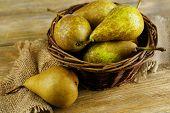 Ripe pears in wicker basket, on wooden background