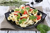 Spaghetti with tomatoes, olives and basil leaves on black plate on napkin on wooden table