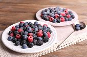 Iced berries on plates, on wooden background