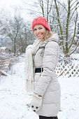 Happy smiling woman standing in winter in snow