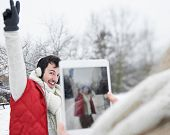 Woman taking pictures of man with headphones with tablet computer in winter