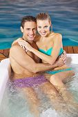 Happy couple in holiday relaxing in whirlpool of a hotel