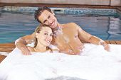 Happy couple relaxing in foam bath in a hotel whirlpool