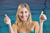 Happy smiling woman in swimming pool holding her thumbs up