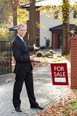 stock photo of house representatives  - Smiling estate agent encouraging to buying house - JPG