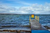 pic of dock a lake  - Empty boat dock overlooking the waters of a gorgeous freshwater lake - JPG