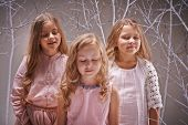 Three calm girls with closed eyes enjoying sounds of fairy winter forest