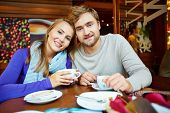 Attractive young man and his girlfriend having coffee in cafe
