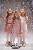 Three amazed girls in smart dresses standing under snowfall in winter forest