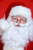 Close-up portrait of Santa Claus. Christmas time. Red background.