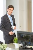 Businessman standing with a coffee, reading a document