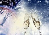 Toasting with champagne against fireworks and clock close to midnight
