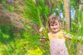young smiling happy girl having fun in palm trees on natural background