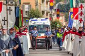 ALBA, ITALY - OCTOBER 05, 2014: Warriors in historic dresses and carabiniers on background march through streets of Alba during traditional annual Medieval Parade.