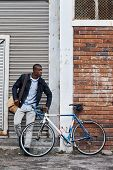 Man relaxing with bicycle in city