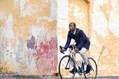 foto of bicycle gear  - Black african mad riding bicycle in urban city commuting with speed and hipster trendy transportation - JPG