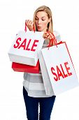Young woman taking advantage of shopping sale with bags isolated on white