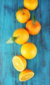 Ripe tangerines and oranges with leaves on wooden background