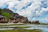 Enchanting Tropical Paradise at Anse Source d'Argent with Large Granite Rocks and Tranquil Lagoon. Captured on Extensive View with Blue and White Sky. Located in the Island of La Digue, Seychelles.