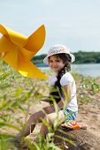 Pretty little girl posing with windmill in park