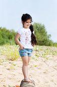 Smiling little girl posing walking along shore
