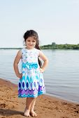Smiling little model posing on river background