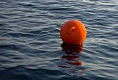 Orange fishing buoy floating in a dark blue sea at sunset