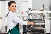 Portrait of happy female chef processing ravioli pasta in machine at commercial kitchen