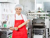 Portrait of smiling female chef holding rolling pin in commercial kitchen