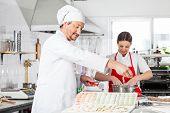 Chefs preparing ravioli pasta at counter in commercial kitchen