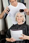 Female client with magazine while male hairstylist setting up her hair at salon