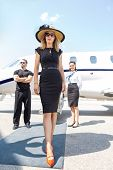 Full length of beautiful woman in elegant dress with bodyguard and airhostess standing against private plane