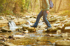 stock photo of crossed legs  - Hiker man with backpack crossing a river on stones in autumn forest view of legs - JPG