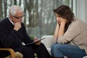 image of psychologist  - Older experienced psychologist diagnosing young troubled woman - JPG