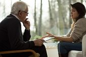 stock photo of psychologist  - Young woman lamenting to her elderly psychologist - JPG