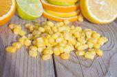 image of sweet-corn  - Sweet corn in front of lime lemon and orange - JPG