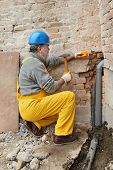 stock photo of chisel  - Home renovation plumber install sewerage pipe at construction site using hammer and chisel - JPG