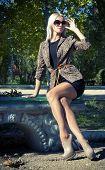 stock photo of slender legs  - Fashion photo of beautiful slender girl model in leopard print jacket with sunglasses - JPG