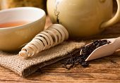 picture of ceremonial clothing  - Horizontal photo of Dry tea leafs near kettle and cup on jute cloth placed on old worn wooden board - JPG